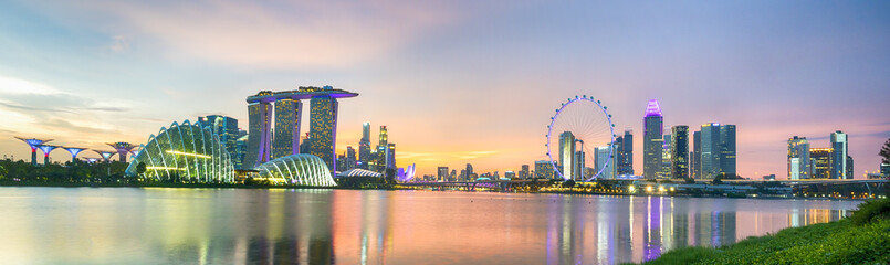 Business city district of Singapore Skyline. At marina bay sand and the garden by the bay on sunset with modern tower building with lighting and colorful of sky cloud.