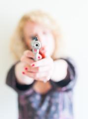 young woman aiming handgun with focus on guns barrel muzzle