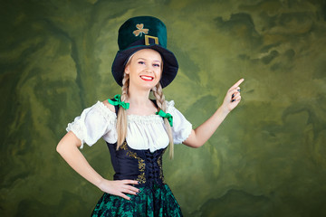 A girl dressed as St. Patrick points with her finger against a green background. St. Patrick's Day.