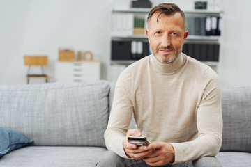 Attractive man relaxing at home on a couch