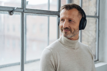 Smiling middle-aged man listening to his music