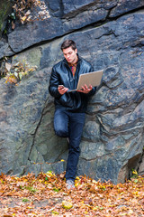 Young American Man working on laptop computer, texting on cell phone outdoor, wearing black leather jacket, pants, gray leather shoes, stands against rocks with fallen leaves on ground in New York..