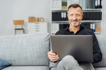 Attractive middle-aged man relaxing with a laptop