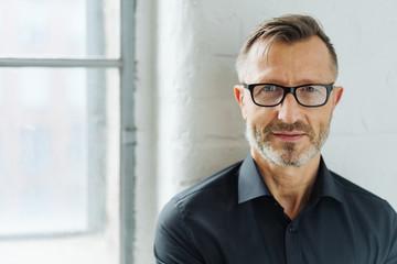 Bearded man wearing glasses looking at camera