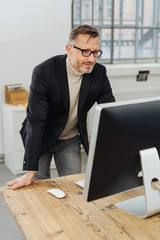 Businessman standing reading a desktop monitor