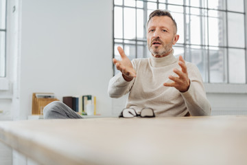 Middle-aged man sitting explaining something