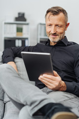 Man sitting reading a handheld tablet