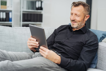 Relaxed middle-aged man reading an e-book