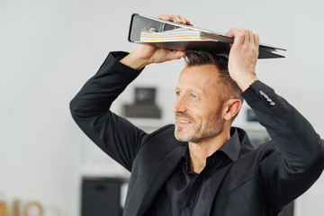 Businessman standing holding a binder on his head
