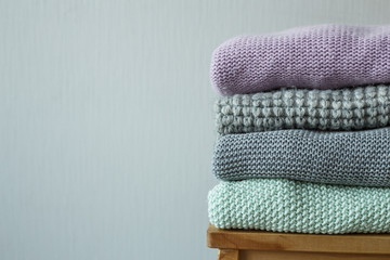 Stack of cozy knitted clothes on a wooden ladder.