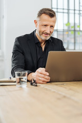 Businessman sitting peering at his laptop screen
