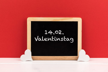 blackboard with hearts and red background with text 14.02. Valentintstag (German for 14.02. Valentine's Day)