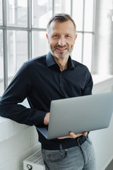Friendly smiling man holding an open laptop