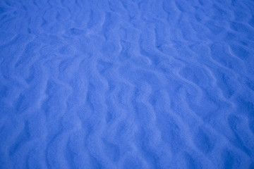 blue background with sand in the shape of sand waves