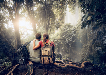 Romantic Couple hikers with backpacks enjoying view waterfall in rain forest