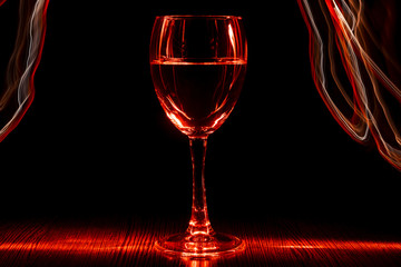 A transparent glass of wine with a liquid. Red blurred bands. Light effect.