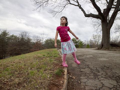 Girl balancing on curb