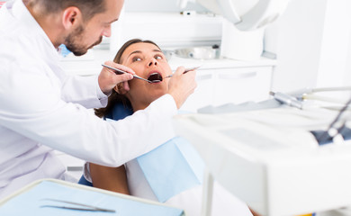 Dentist is treating woman patient which is sitting chair in clinic