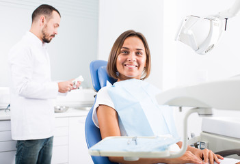 Young female is sitting satisfied after treatment in dental office
