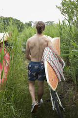 Rear view of shirtless man carrying surfboard while walking amidst plants with bicycle on field