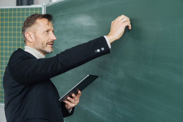 Middle-aged male teacher writing on a chalkboard