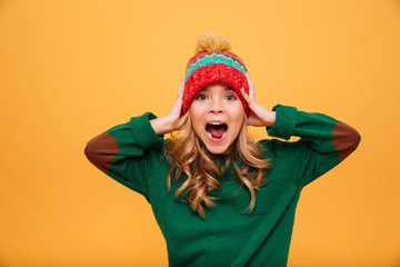 Shocked Screaming Young girl in sweater and hat holding head