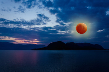 Super Blue Blood Moon Eclipse Lunar Color Sky on background of ocean and mountains nature in beach