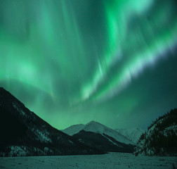 Low angle majestic view of aurora borealis over mountains during winter