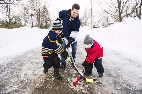 Father and two sons playing hockey
