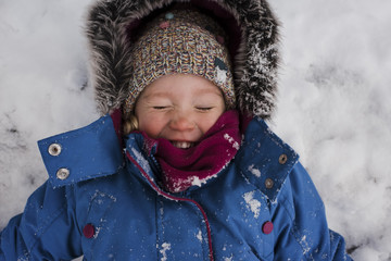 High angle view of smiling girl with eyes closed lying on snow covered field