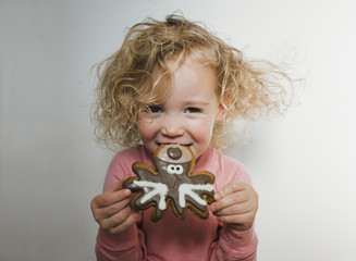 Portrait of girl holding cookie while standing against white wall at home