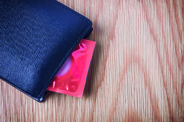 Condom put inside man wallet, Safe sex concept