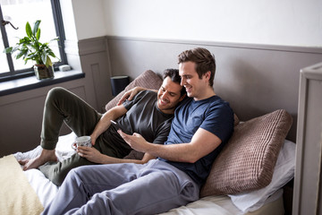 Young male couple looking at smarphone together