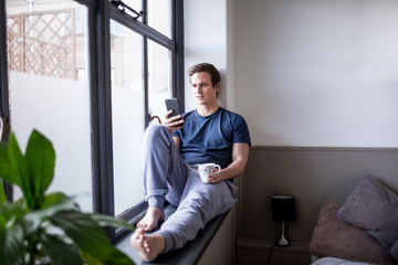 Young male with smartphone and coffee