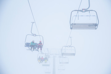 Ski lift in ski resort. Silhouette of skiers, white background