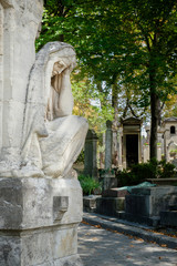 Statue of a sad woman on the Pere Lachaise cemetery in Paris