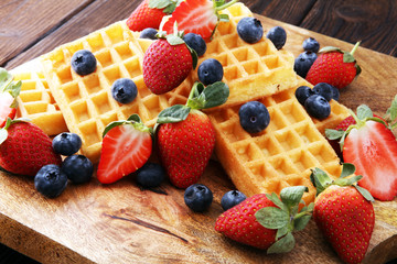 Board of belgian waffles with fresh berries on wooden background