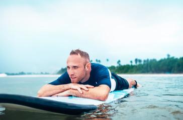 Man surfer rests lying on surfboard