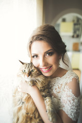 Young beautiful bride with a cat in her arms, the morning before the wedding