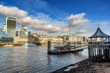 A view across the River Thames with the financial skyscrapers of the city of London, UK