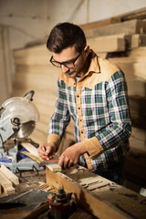 Young carpenter working in his shop