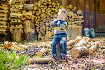 the boy on the background of wooden logs