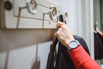 woman put backpack on wall hanger