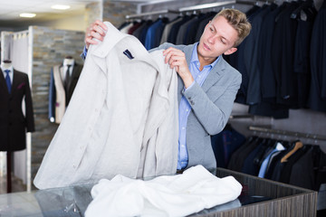 Man buyer in jacket choosing shirt