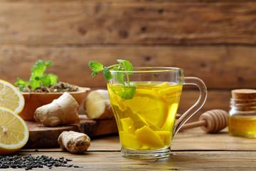 infuso di limone e zenzero su sfondo un bicchiere con bevanda calda