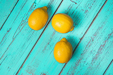 Yellow lemons on a rustic blue table. Vintage concept