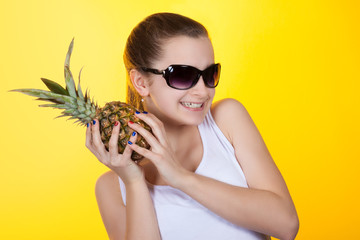 girl teenager laughing and holding a pineapple in his hands.