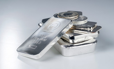 Silver bullion. Cast and minted bars and coins on a gray background. Selective focus.