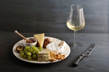 cheese plate, wine and cheese knife on dark background