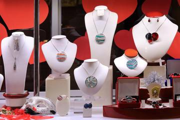 Fototapeta Naszyjniki, kolczyki i pierścień na białych popiersiach w sklepie jubilerskim. obraz